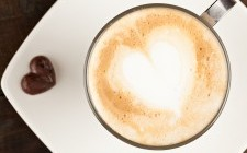Beautifuly decorated cup of cappucino and chocolate heart, against polished table top