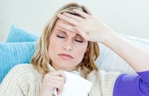 Sick woman with headache lying on the sofa in the living-room at home